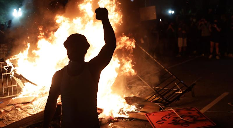 Demonstrators stand around a fire during a protest on May 31 near the White House in response to the killing of George Floyd. (Photo: Alex Wong via Getty Images)