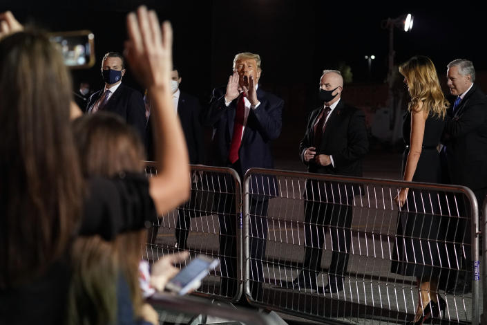 President Donald Trump gestures to supporters before boarding Air Force One at Nashville International Airport after participating in the presidential debate, Thursday, Oct. 22, 2020, in Nashville, Tenn., as first lady Melania Trump watches. (AP Photo/Evan Vucci)