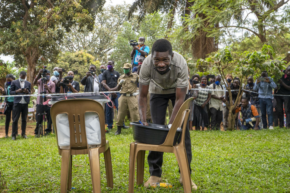 Uganda's leading opposition challenger Bobi Wine fills his ballot before voting in Kampala, Uganda, Thursday, Jan. 14, 2021. Ugandans are voting in a presidential election tainted by widespread violence that some fear could escalate as security forces try to stop supporters of Wine from monitoring polling stations.(AP Photo/Jerome Delay)