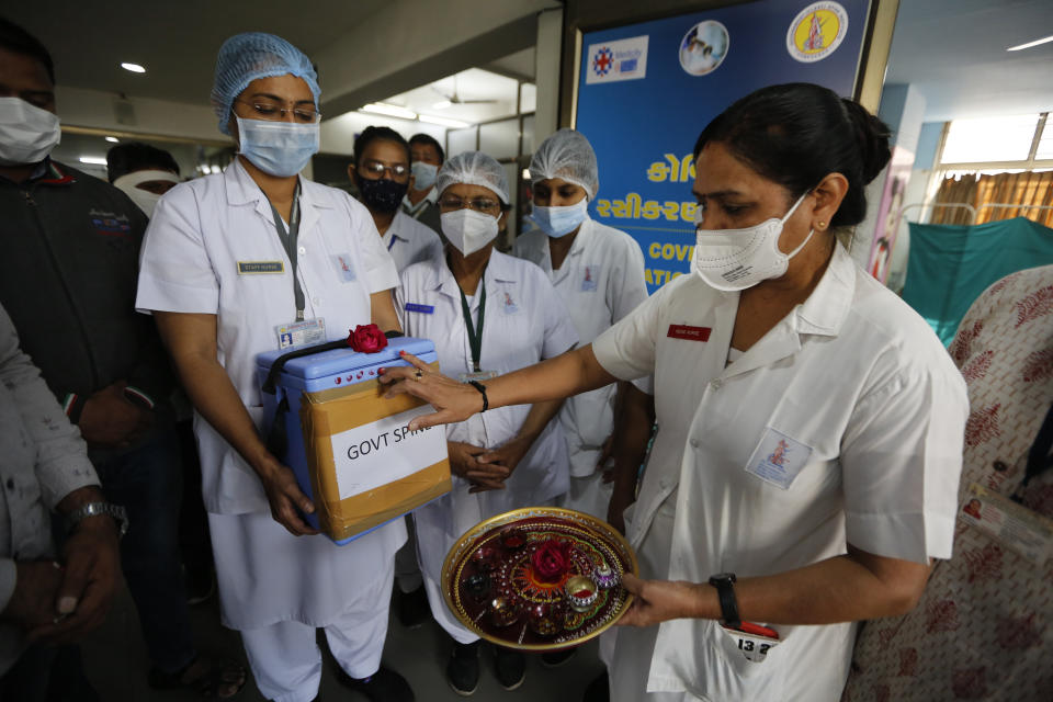 <p>A nurse, right, performs rituals to a box containing COVID-19 vaccines upon its arrival at a government Hospital in Ahmedabad,</p> (AP)