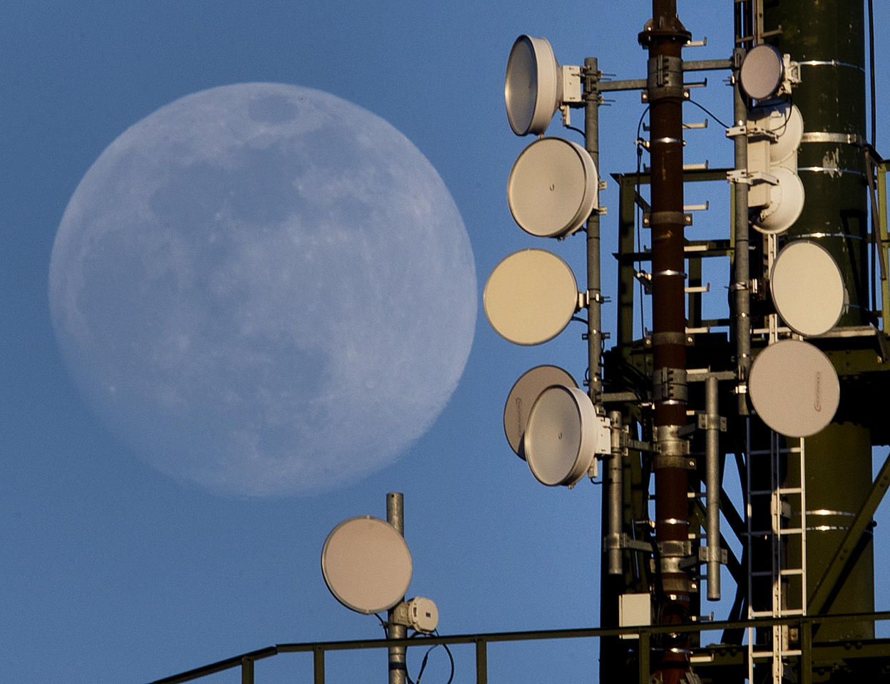 <p>The moon rises behind a mobile radio mast in Wachenbuchen near Frankfurt, Germany, Tuesday, March 19, 2019. (AP Photo/Michael Probst) </p>
