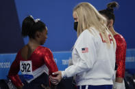 FILE - In this July 27, 2021 file photo, Simone Biles, of the United States, talks with her coach after performing on the vault during the artistic gymnastics women's final at the 2020 Summer Olympics, in Tokyo. Biles and Naomi Osaka are prominent young Black women under the pressure of a global Olympic spotlight that few human beings ever face. But being a young Black woman -- which, in American life, comes with its own built-in pressure to perform -- entails much more than meets the eye.(AP Photo/Gregory Bull, File)