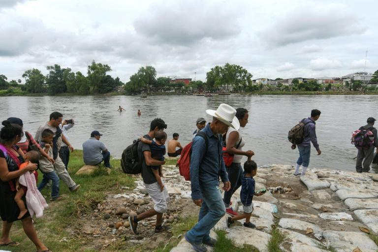 Honduran migrants prepare to board makeshift rafts to cross the Suchiate River on the border between Guatemala and Mexico in Ciudad Tecun Uman, Guatemala