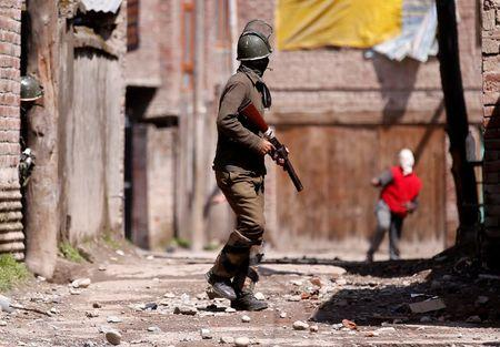 A Kashmiri demonstrator throws a stone towards an Indian policeman during a protest against by-polls in Srinagar
