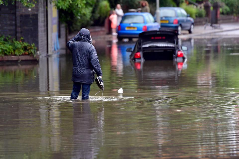 A man carries his shoes as he walks through flood water on Crossley Road near Levenshulme in Manchester, England (Picture: Getty)