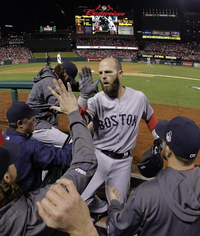 Boston Red Sox second baseman Dustin Pedroia is congratulated by teammates after scoring on an RBI double by Boston Red Sox designated hitter David Ortiz during the first inning of Game 5 of baseball's World Series against the St. Louis Cardinals Monday, Oct. 28, 2013, in St. Louis. (AP Photo/Matt Slocum)
