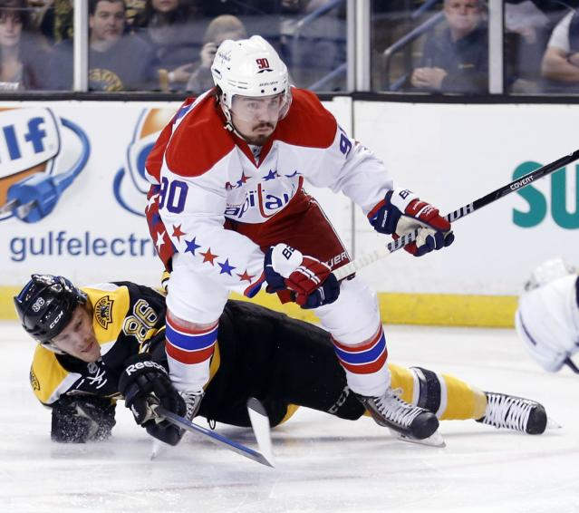 Boston Bruins' Kevan Miller (86) falls while defending against Washington Capitals' Marcus Johansson (90) in the first period of an NHL hockey game in Boston, Saturday, March 1, 2014. (AP Photo/Michael Dwyer)