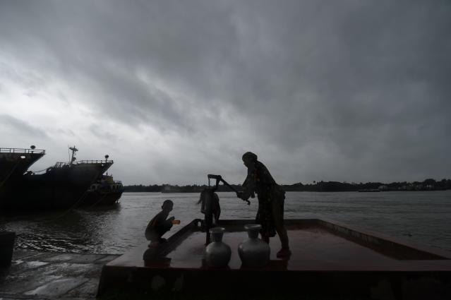 """A family collects drinking water froma water pump ahead of the expected landfall of cyclone Amphan, in Khulna on May 20, 2020. - Several million people were taking shelter and praying for the best on Wednesday as the Bay of Bengal's fiercest cyclone in decades roared towards Bangladesh and eastern India, with forecasts of a potentially devastating and deadly storm surge. Authorities have scrambled to evacuate low lying areas in the path of Amphan, which is only the second """"super cyclone"""" to form in the northeastern Indian Ocean since records began. (Photo by Munir uz Zaman / AFP) (Photo by MUNIR UZ ZAMAN/AFP via Getty Images)"""