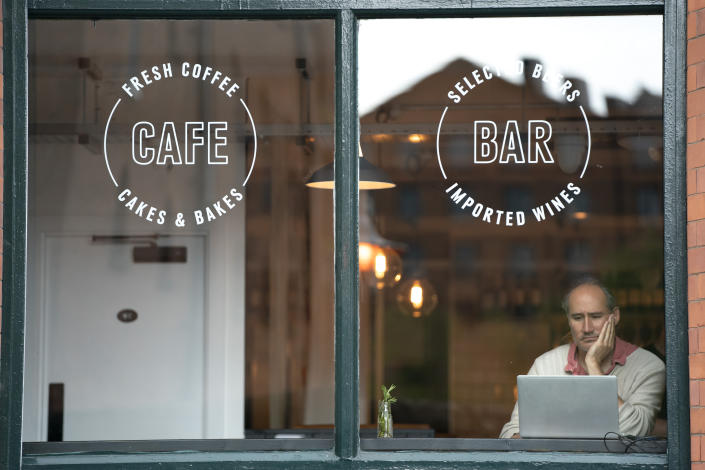A man sits at his laptop in a cafe, as pubs, cafes and restaurants in England reopen indoors under the latest easing of the coronavirus lockdown, in Manchester, England, Monday, May 17, 2021. Pubs and restaurants across much of the U.K. are opening for indoor service for the first time since early January even as the prime minister urged people to be cautious amid the spread of a more contagious COVID-19 variant. (AP Photo Jon Super)