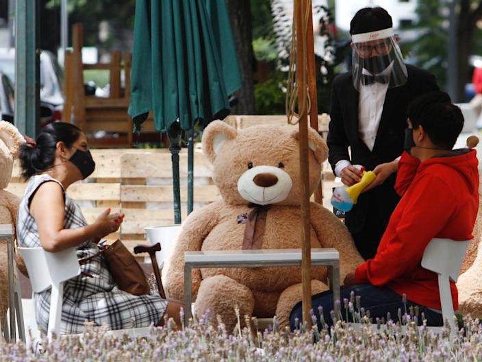 """Owners of restaurants put Giant teddy bears on the chairs as an attempt to get customers to respect social distancing. <p class=""""copyright"""">Leonardo Casas / Eyepix Group/Barcroft Media via Getty Images</p>"""