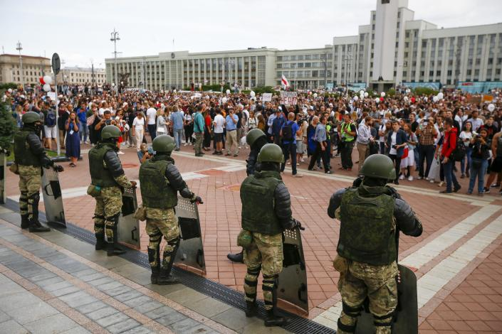People gather in front of soldiers guarding the Belarusian Government building during a rally in Minsk, Belarus, Friday, Aug. 14, 2020. Some thousands of people have gathered in the centre of the Belarus capital, Minsk, in a show of anger over a recent brutal police crackdown on peaceful protesters that followed a disputed presidential election.(AP Photo/Sergei Grits)