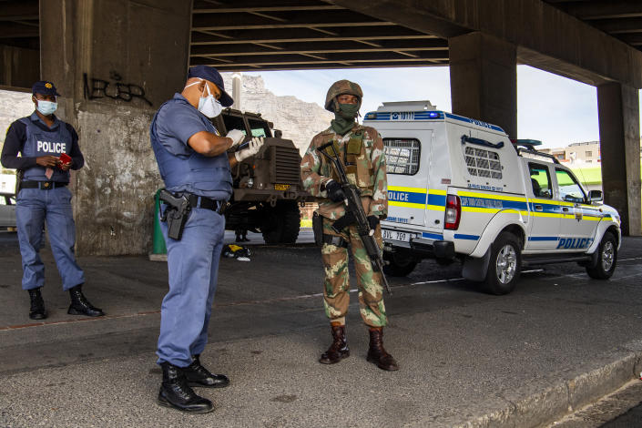 A policeman and soldier man a roadblock in Cape Town, South Africa, Friday, March 27, 2020, after South Africa went into a nationwide lockdown for 21 days in an effort to mitigate the spread to the coronavirus. The new coronavirus causes mild or moderate symptoms for most people, but for some, especially older adults and people with existing health problems, it can cause more severe illness or death(AP Photo)