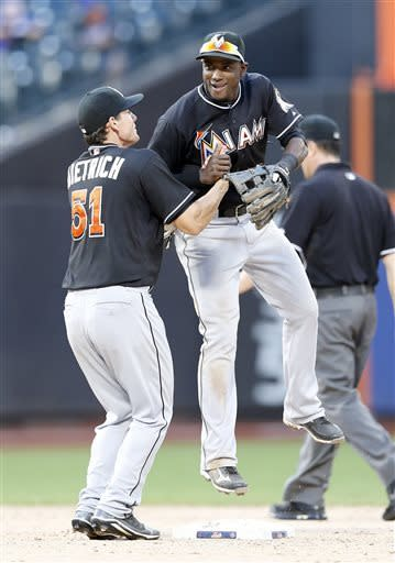 Miami Marlins shortstop Adeiny Hechavarria (3) leaps into teammate Derek Dietrich (51) as they celebrate the last out in their 2-1 win over the New York Mets in a 20-inning baseball game at Citi Field in New York, Saturday, June 8, 2013. (AP Photo/Paul J. Bereswill)