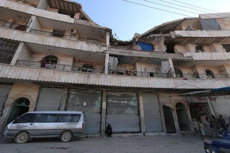 Residents stand on the balconies of a damaged building in Manbij, in Aleppo Governorate, Syria, August 9, 2016. REUTERS/Rodi Said