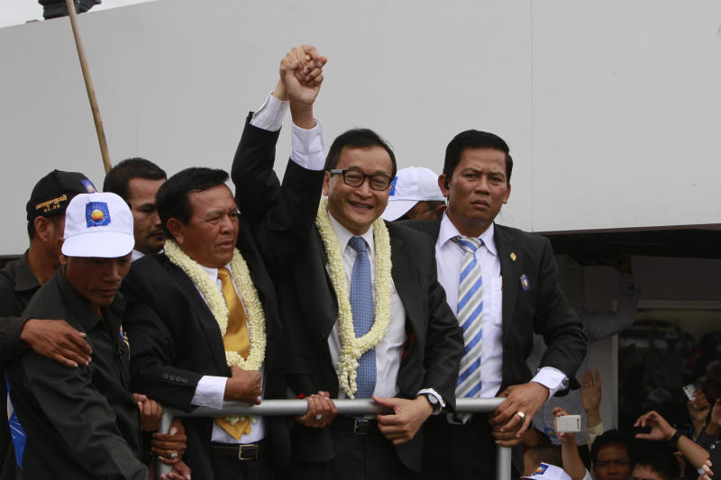 Sam Rainsy, center, president of Cambodia National Rescue Party (CNRP) holds hands with his party's Vice President Kem Sokha on his arrival at Phnom Penh International Airport, in Phnom Penh, Cambodia, Friday, July 19, 2013. Thousands of cheering supporters greeted Cambodian opposition leader Rainsy as he returned from self-imposed exile Friday to spearhead his party's election campaign against well-entrenched Prime Minister Hun Sen. (AP Photo/Heng Sinith)