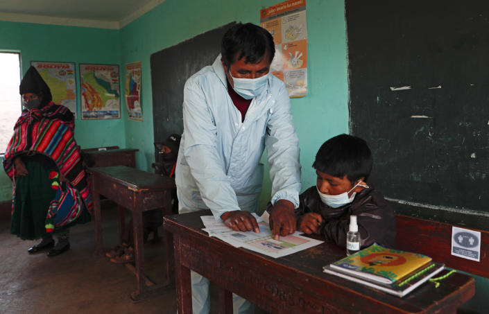Teacher Manuel Layme works with a student, both wearing new protective uniforms, during the first week back to in-person classes amid the COVID-19 pandemic, as a parent, left, observes class in the Aymara Indigenous community near Jesus de Machaca, Bolivia, Thursday, Feb. 4, 2021. (AP Photo/Juan Karita)
