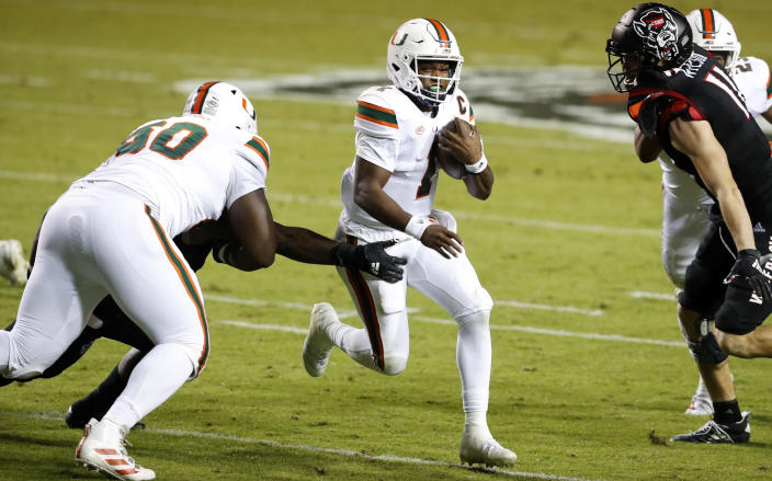 Miami quarterback D'Eriq King (1) runs past North Carolina State linebacker Isaiah Moore, obscured at left, during the first half of an NCAA college football game Friday, Nov. 6, 2020, in Raleigh, N.C. (Ethan Hyman/The News & Observer via AP, Pool)