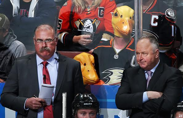 """Two fans wear duck masks as assistant coach, Paul MacLean, and head coach Randy Carlyle of the <a class=""""link rapid-noclick-resp"""" href=""""/nhl/teams/ana/"""" data-ylk=""""slk:Anaheim Ducks"""">Anaheim Ducks</a> watch the game against the St. Louis Blues on March 15, 2017 at Honda Center in Anaheim, California. (Getty Images)"""