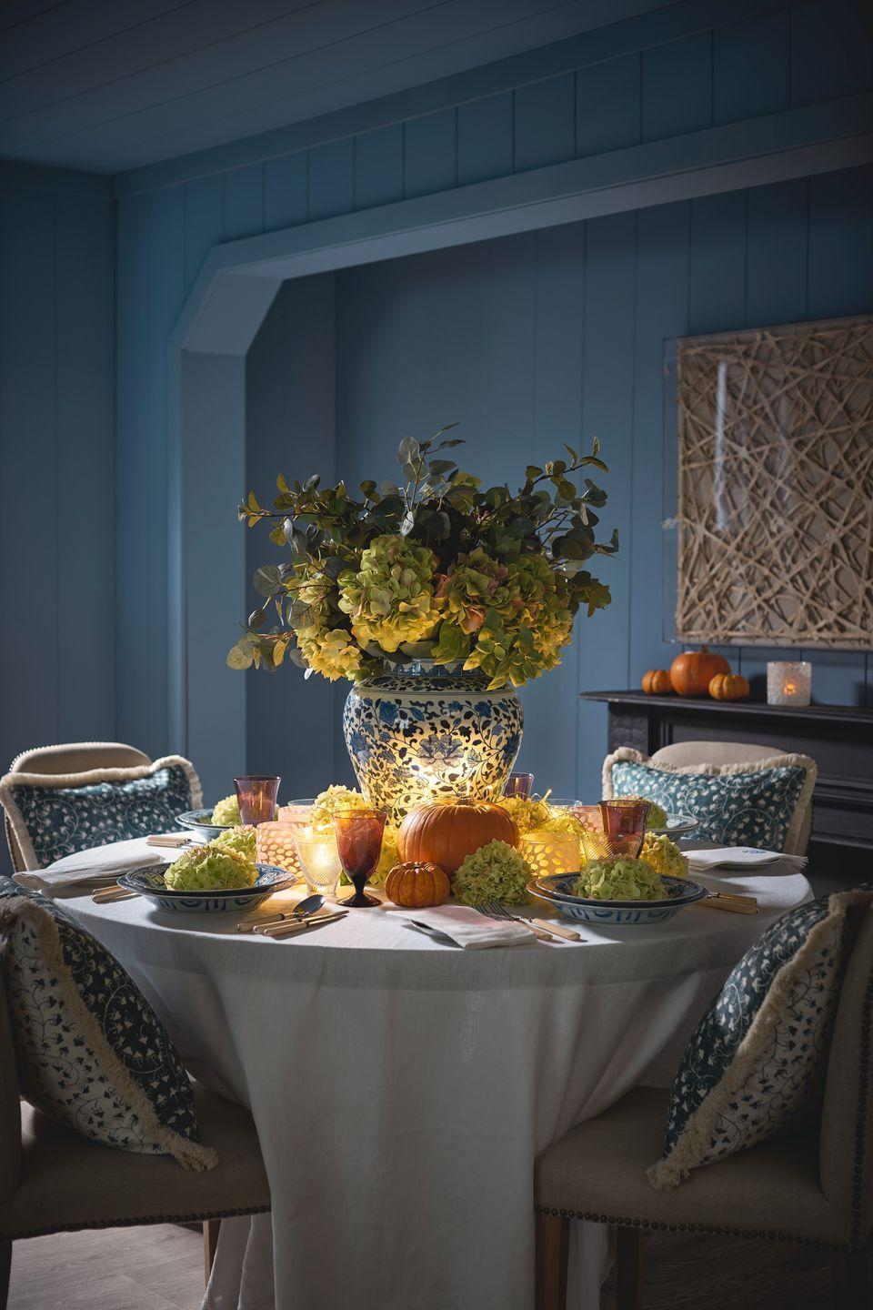 """<p><a href=""""https://www.oka.com/"""" rel=""""nofollow noopener"""" target=""""_blank"""" data-ylk=""""slk:OKA"""" class=""""link rapid-noclick-resp"""">OKA</a> uses a romantic blue-and-white color palette with pops of orange and unexpected lime green for an elegant fall table.</p>"""