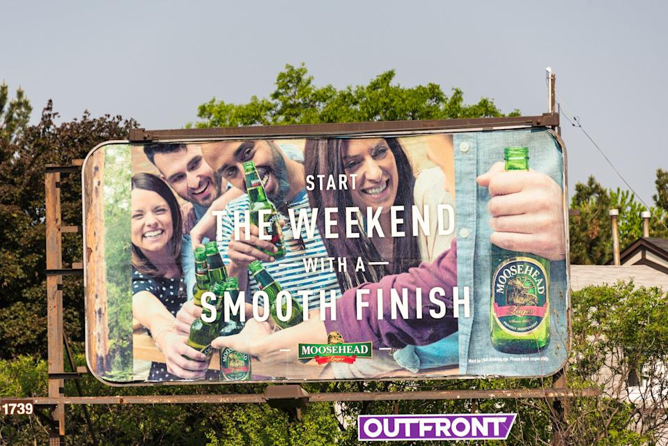 TORONTO, ONTARIO, CANADA - 2015/05/28: Moosehead beer billboard advertisement with two women and two men holding Moosehead beer bottles   Outfront is a full-service Out-of-Home advertising company, OUTFRONT Media offers over 12,000 advertising display faces in superior locations in all of Canada's top 10 markets. (Photo by Roberto Machado Noa/LightRocket via Getty Images)