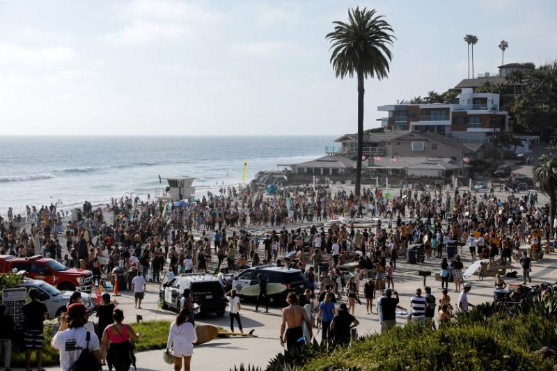 "People and surfers gather at Moonlight Beach in Encinitas, California, for the ""Paddle out for Unity"" event in support of Black Lives Matter, following the death of George Floyd"