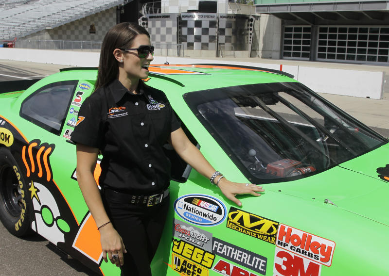 Race car driver Danica Patrick waits by a car she drove laps with journalist/television personality Katie Couric during a break in interviews at the Indianapolis Motor Speedway in Indianapolis, Tuesday, July 10, 2012. (AP Photo/Michael Conroy)