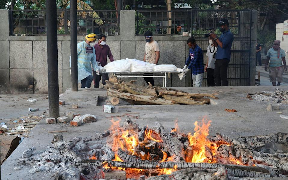 Volunteers carry a Covid-19 victim at a cremation ground in New Delhi - Shutterstock