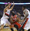 Houston Rockets' James Harden (13) works against Portland Trail Blazers' Thomas Robinson (41) and Robin Lopez (42) during the first half of game six of an NBA basketball first-round playoff series game in Portland, Ore., Friday May 2, 2014. (AP Photo/Greg Wahl-Stephens)