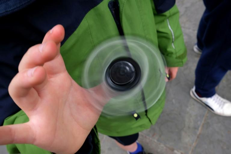 A boy playing with a fidget spinner