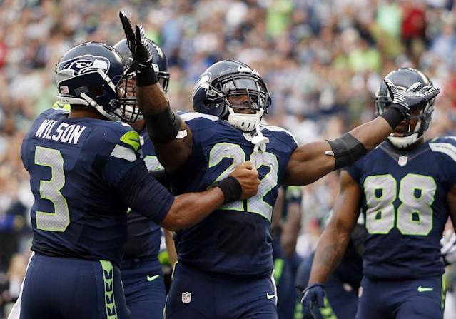 Seattle Seahawks quarterback Russell Wilson, left, celebrates with running back Robert Turbin (22) after Turbin scored a touchdown against the San Diego Chargers in the first half of a preseason NFL football game, Friday, Aug. 15, 2014, in Seattle. (AP Photo/John Froschauer)