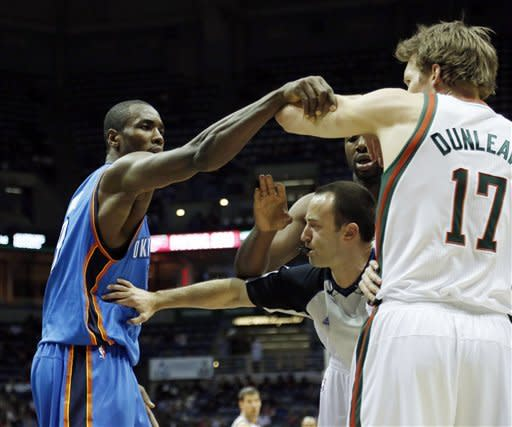 An official gets in the middle of Oklahoma City Thunders' Serge Ibaka, left, and Milwaukee Bucks' Mike Dunleavy during the first half of an NBA basketball game Monday, April 9, 2012, in Milwaukee. (AP Photo/Jeffrey Phelps)
