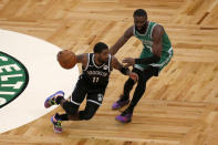 Brooklyn Nets guard Kyrie Irving (11) drives against Boston Celtics guard Jaylen Brown (7) during the first half of an NBA preseason basketball game, Friday, Dec. 18, 2020, in Boston. (AP Photo/Mary Schwalm)