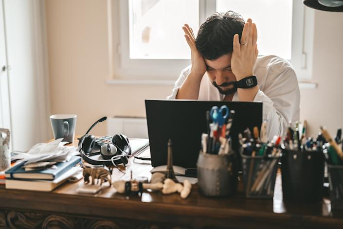 Tired frustrated exhausted businessman working from home online sitting at home office with laptop during quarantine and self isolation period at pandemic. Crisis management. Despair of market falling down.