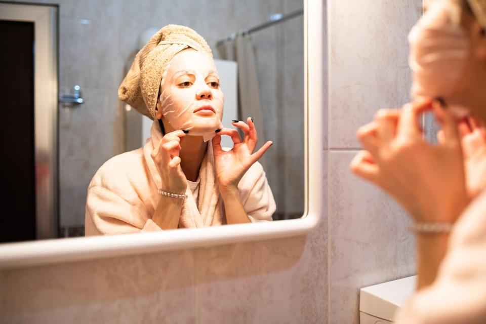A beautiful young woman is applying a sheet mask in front of the mirror