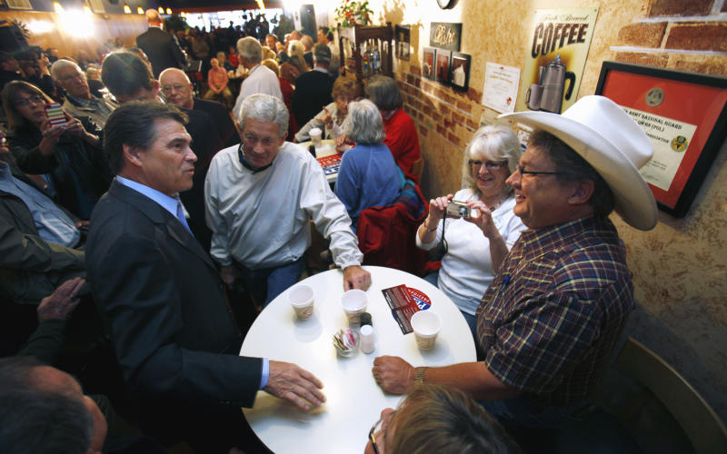 Republican presidential candidate, Texas Gov. Rick Perry talks with Arvin Peterson, of Knoxville, Iowa, right, and others, during a campaign stop at Uncle Nancy's Coffee Shop in Newton, Iowa, Friday, Sept 16, 2011.  (AP Photo/Charlie Neibergall)