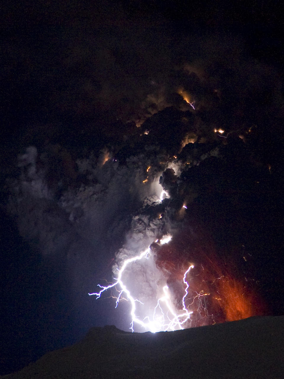 Lighting seen amid the lava and ash erupting from the vent of the Eyjafjallajokull volcano in central Iceland early morning Sunday April 18 2010 as it continues to vent into the skies over Europe. Low-energy lightning is sometimes active during eruptions, arcing between particles as they exit the volcanic vent at around 100 metres per second. The dramatic volcanic eruption which has closed Europe's airspace for days has entered a new phase - producing less smoke but bubbling with lava and throwing up chunks of molten rock. (AP Photo/ Jon Pall Vilhelmsson