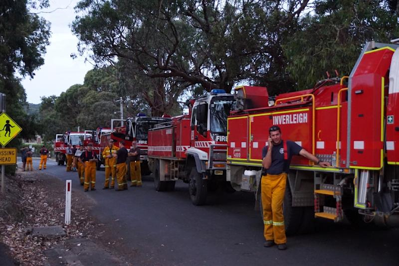 Volunteer fire-fighters take a break while fighting fires in a scenic area along Victoria's Great Ocean Road southwest of Melbourne, on December 26, 2015 (AFP Photo/Keith Pakenham)