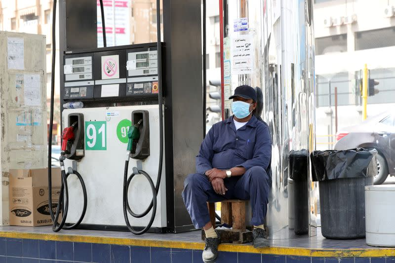 A gas station worker wearing a protective face mask sits next to a petrol station, after Saudi Arabia imposed a temporary lockdown on the province of Qatif following the spread of coronavirus, in Qatif