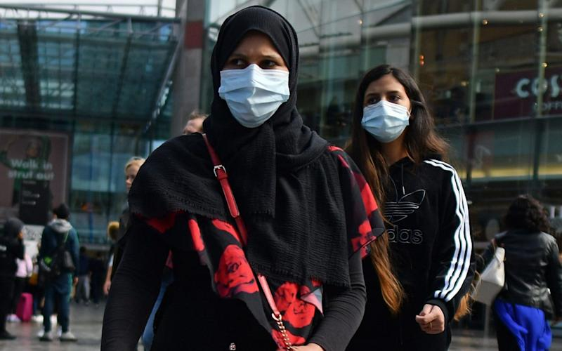 (FILES) In this file photo taken on August 22, 2020 Shoppers wearing protective face coverings walk past shops in Birmingham, central England. - Authorities in Britain's second city of Birmingham announced new coronavirus restrictions Friday, September 11, as the nation's reproduction rate, or R number, exceeded 1.0 for the first time since March. (Photo by JUSTIN TALLIS / AFP) (Photo by JUSTIN TALLIS/AFP via Getty Images) - JUSTIN TALLIS/AFP