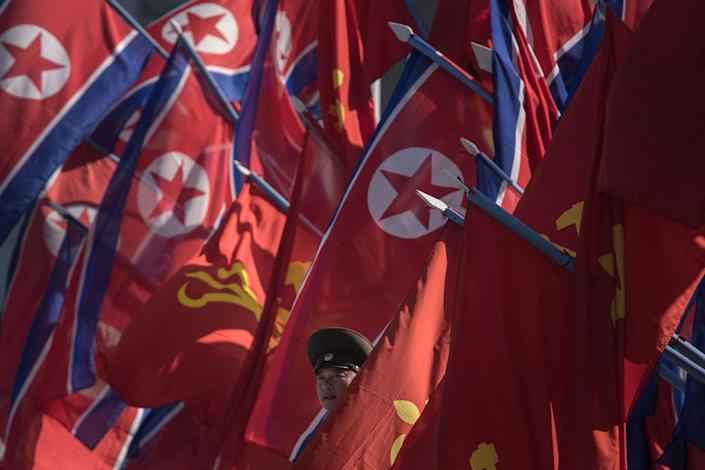 A Korean People's Army soldier stands between flags in Pyongyang on April 13, 2017. (Photo: Ed Jones/AFP/Getty Images)