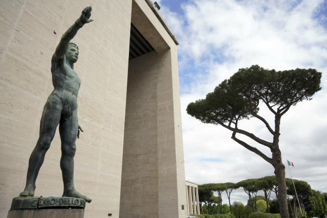 """A bronze sculpture by Italo Griselli, known under the Fascist regime as """"Saluto Fascista"""" (Fascist Salute) and after the war renamed Genio dello Sport (Genius of Sport), stands at the entrance of a fascist architecture building in the EUR neighborhood, in Rome, Monday, May 6, 2019. Mussolini transformed Rome's urban landscape with grand construction projects like EUR, a new city district that was originally designed as celebration of fascism for a world fair in 1942. The fair was canceled due to WWII and construction was halted but resumed after the war. (AP Photo/Andrew Medichini)"""