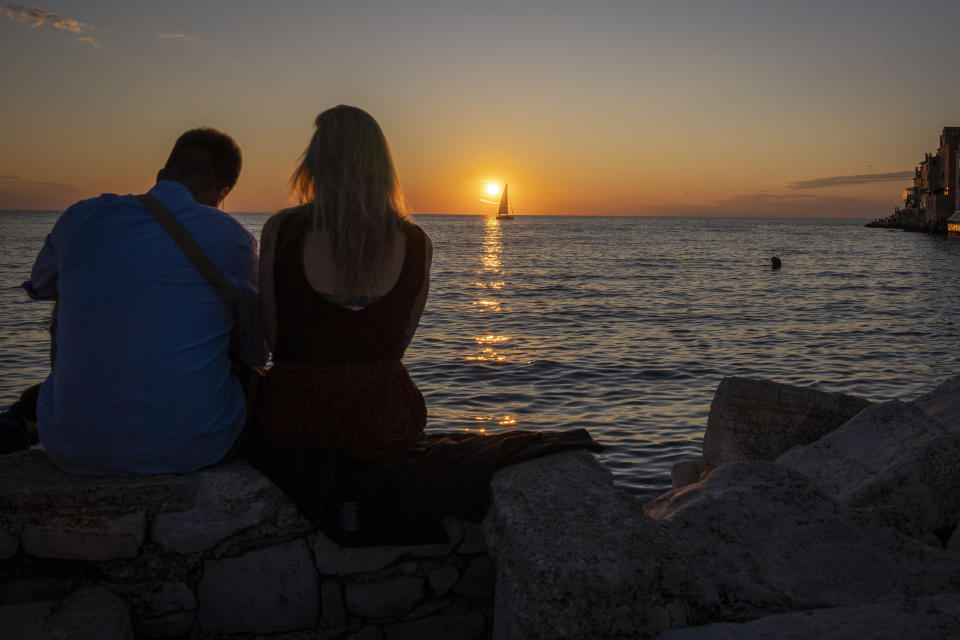 A couple enjoy the sunset on the seafront in the Adriatic town of Rovinj, Croatia, Friday, Aug. 27, 2021. Summer tourism has exceeded even the most optimistic expectations in Croatia this year. Beaches along the country's Adriatic Sea coastline are swarming with people. Guided tours are fully booked, restaurants are packed and sailboats were chartered well in advance. (AP Photo/Darko Bandic)