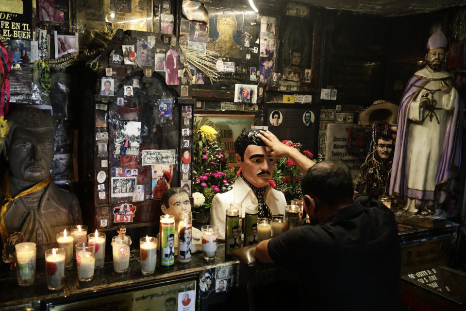 A man touches a statue of Jesus Malverde inside the shrine dedicated to the patron saint of drug dealers in Culiacan, Sinaloa state, Mexico, Thursday, April 8, 2021. Jesus Malverde is worshipped by many drug traffickers in this region which is also known as the cradle of drug trafficking in the country. (AP Photo/Eduardo Verdugo)