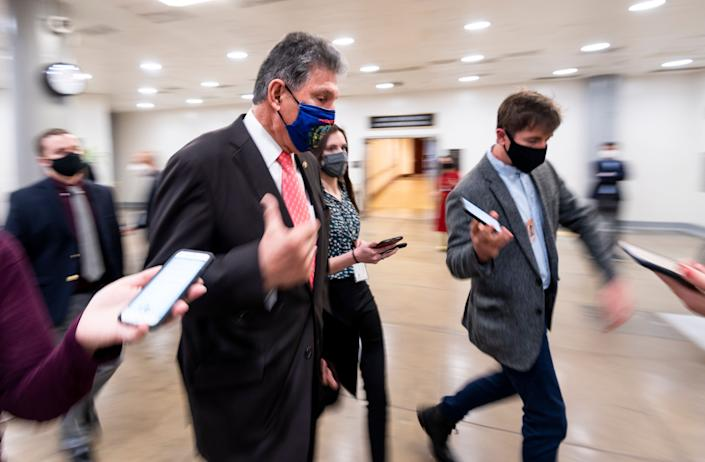 Sen. Joe Manchin (D-W.Va.) speaks with reporters in the Senate subway as he arrives for a vote in the Capitol on Wednesday, March 24. (Photo: Bill Clark via Getty Images)
