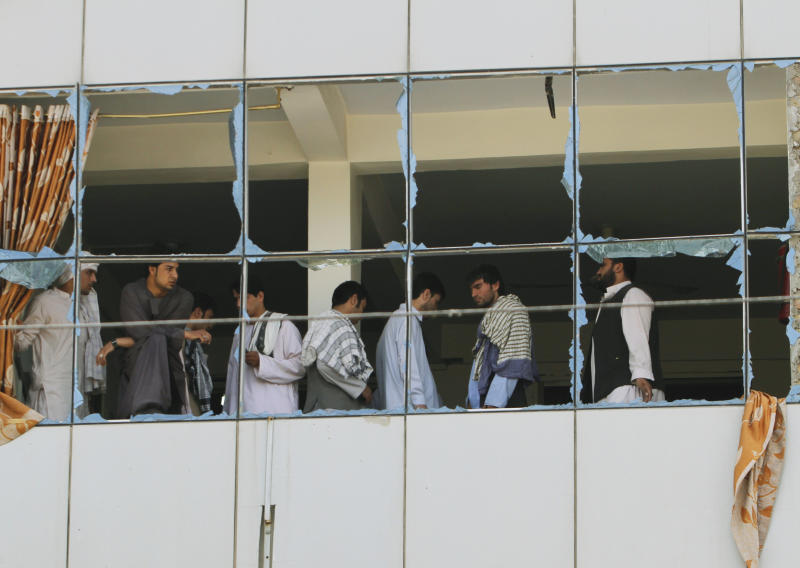 Afghan men look through windows of a New Kabul Bank branch building at the site of a suicide bomb explosion in Kandahar province, southwest of Kabul, Afghanistan, Saturday, Aug. 31, 2013. A suicide bomber detonated his explosives near a police checkpoint and the bank in southern Afghanistan on Saturday, killing several people, officials said. Most of the victims were civilians. Along with the badly damaged branch building, several small shops and vehicles were damaged. (AP Photo/Allauddin Khan)