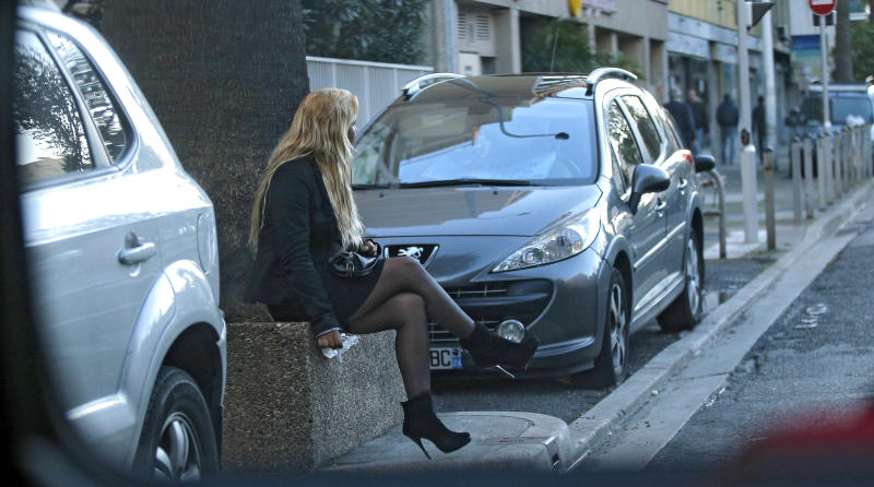 "A prostitute waits for a client in a street of Nice southern France, Thursday, Nov 21, 2013. France's government is pushing one of Europe's toughest laws against prostitution and sex trafficking, and other countries are watching closely. Advocates hope that a draft French law going to parliament Wednesday will help change long-held attitudes toward the world's oldest profession _ by punishing the customer and protecting the prostitute. But the bill is facing resistance in a country with a libertine reputation and a Mediterranean macho streak, and has prompted petitions defending those who buy sex. Signatories include screen icon Catherine Deneuve _who played a prostitute in the cult film ""Belle de Jour"" _ and crooner Charles Aznavour. (AP Photo)"