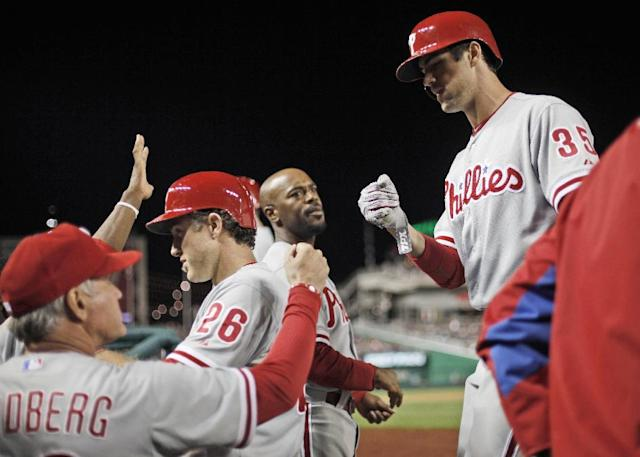 Philadelphia Phillies manager Ryne Sandberg, left, greets Chase Utley (26) and Cole Hamels (35) in the dugout after they scored on triple hit by Carlos Ruiz during the fifth inning of a baseball game at Nationals Park, Saturday, Sept. 14, 2013, in Washington. (AP Photo/Pablo Martinez Monsivais)
