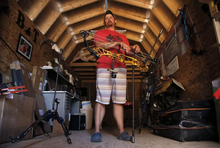 """FILE - In this April 30, 2020, file photo, U.S. Olympic Team archer Brady Ellison pauses with a compound bow at his range on his farm in Miami, Ariz. The playbook for athletes provides a guide to a """"safe and successful Games"""" for the Tokyo Olympics. It's filled with """"cannots"""" and """"do nots,"""" meaning a once-in-a-liftetime opportunity will be a whole lot less fun. (AP Photo/Ross D. Franklin, File)"""