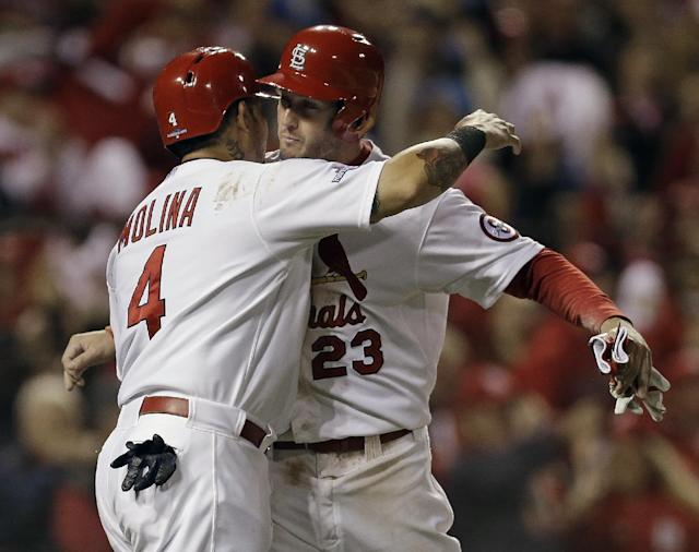 St. Louis Cardinals' David Freese and Yadier Molina celebrate after both scored on a hit by Shane Robinson during the third inning of Game 6 of the National League baseball championship series against the Los Angeles Dodgers Friday, Oct. 18, 2013, in St. Louis. (AP Photo/Jeff Roberson)