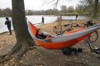Kristina Rudic lies in a hammock she strung between two trees while using an application on her cell phone to learn Spanish as her Peruvian boyfriend, left, fishes in the lake in Prospect Park, Sunday, Nov. 15, 2020, in the Brooklyn borough of New York. (AP Photo/Kathy Willens)